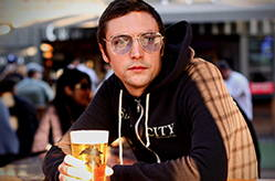 Reid is modeling his favorite Smog City zip up and enjoying a pint glass of pilsner at our SteelCraft location. He is wearing light colored glasses and gazing into the distance.