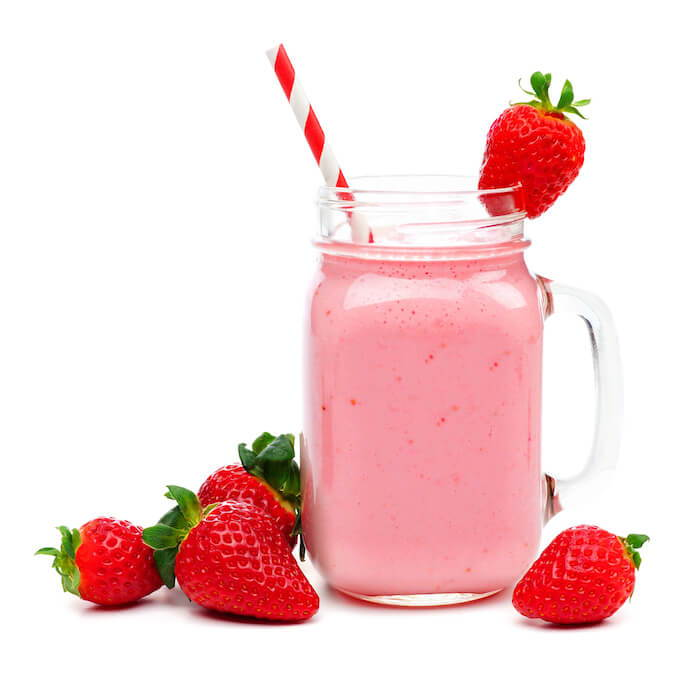 Strawberry protein shake with strawberries on the side