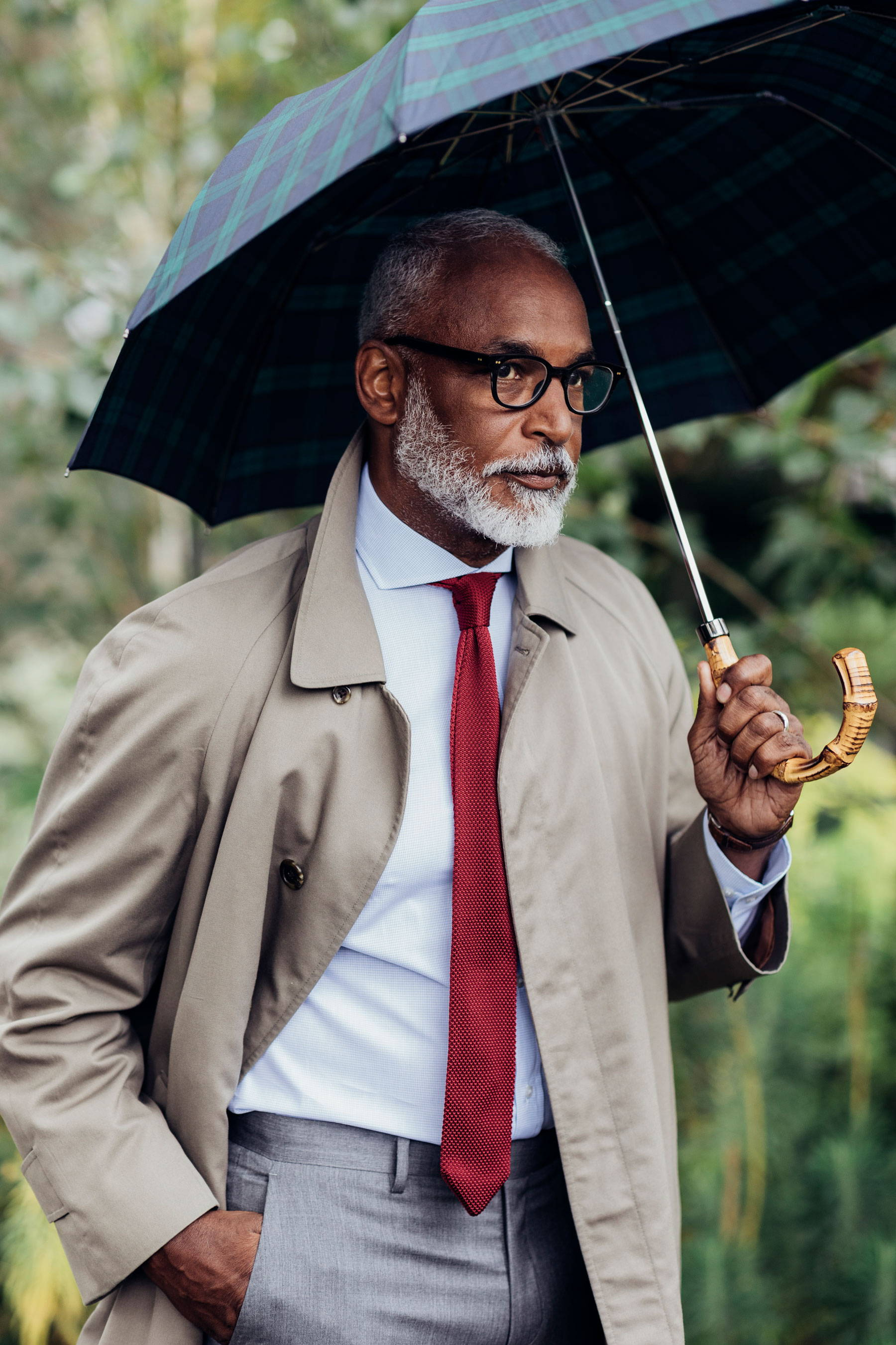 Man with red tie holding umbrella