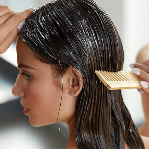 woman combing conditioner through hair