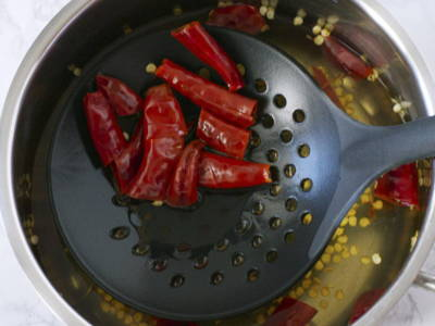 Using a strainer with bigger holes, scoop out the boiled dried chillies. The seeds will sink to the bottom of the pot.