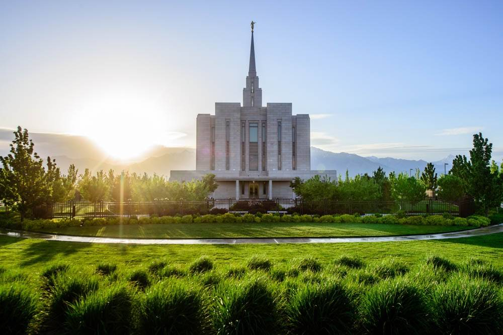 LDS art photo of the Oquirrh Mountain Temple and green grounds as the sun peeks over the mountains.