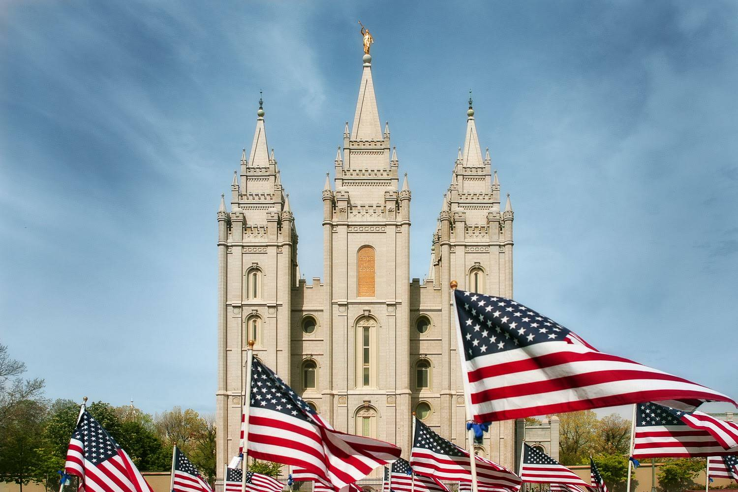 PHoto of hte Salt Lake City Temple with rows of US flags in the forefront.