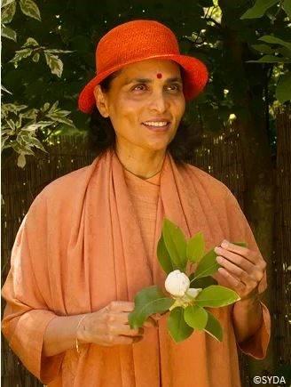 Gurumayi Chidvilasananda smiling wearing orange hat and holding white flowers