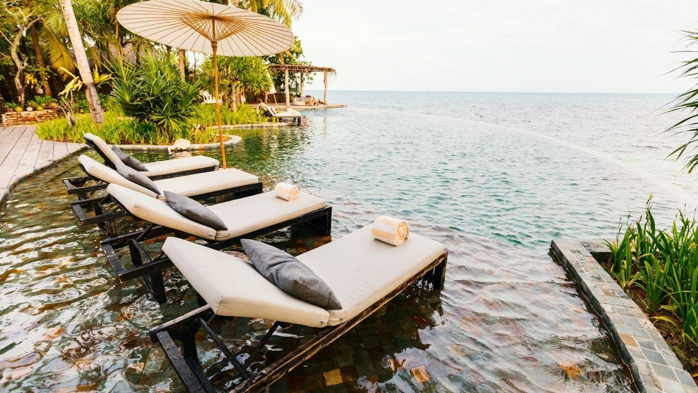 Four white lounge chairs on edge of infinity pool overlooking ocean