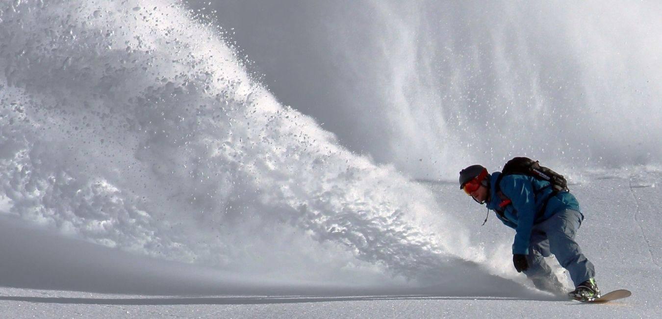 Une photo d'un snowboardeur spécialisé en freeride faisant une courbe qui fait voler de la poudreuse en quantité, on le voit en splitboard sur l'arrière de la planche afin de ne pas tomber.