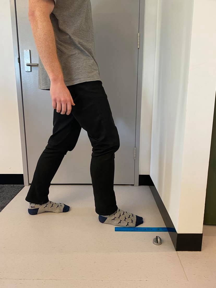Preparing for a lunge to measure knee to wall for ankle dorsiflexion and tight calves