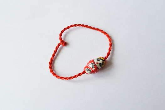 Браслет из красных шелковых нитей с керамической бусиной матрешкой.