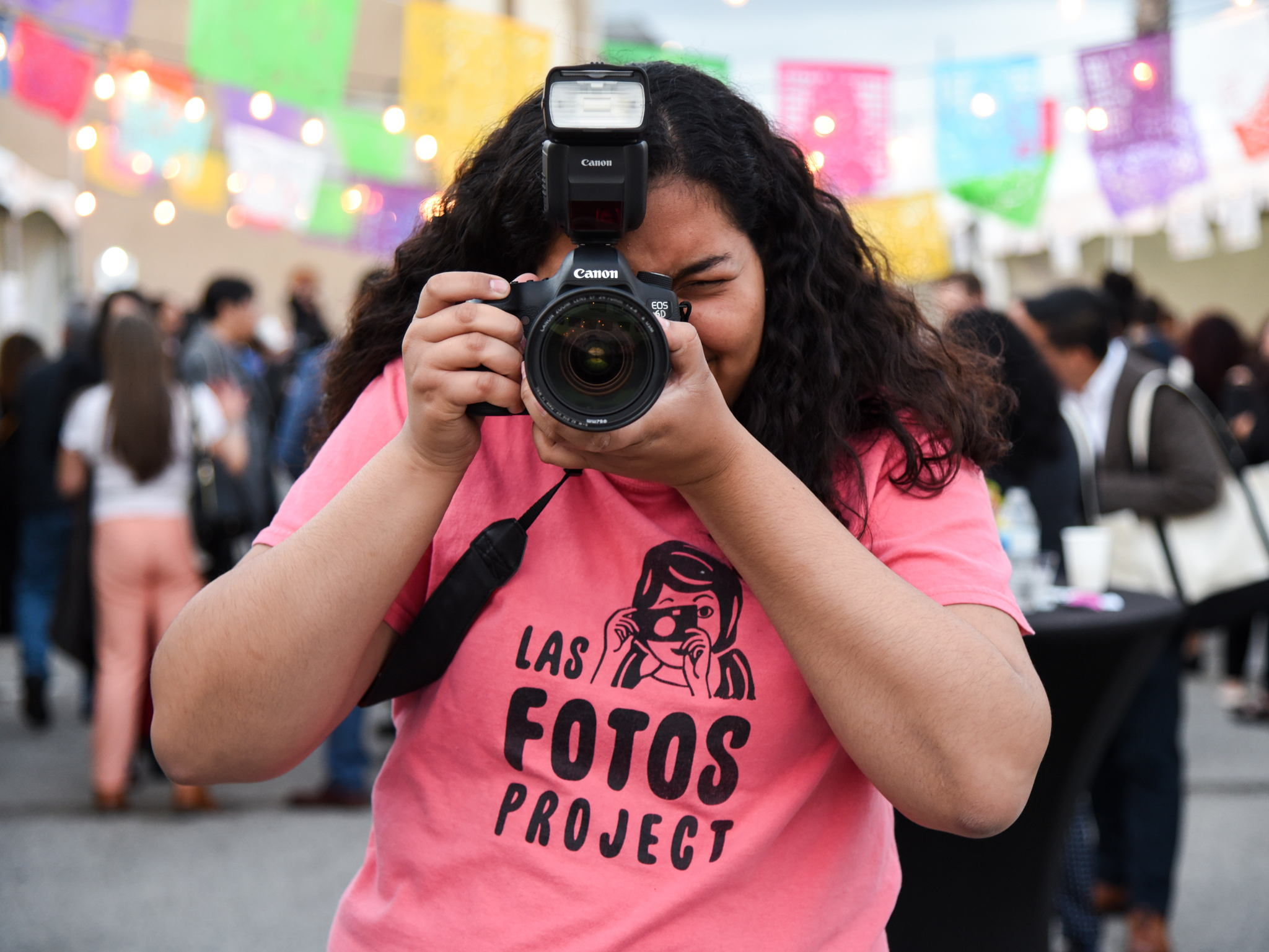"""A girl wearing a pink """"Las Fotos Project"""" t-shirt holds a DSLR camera up to her face"""