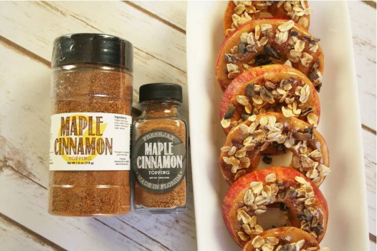 Two bottles of FreshJax Organic Maple Cinnamon topping next to a plate of maple cinnamon peanut butter apples.