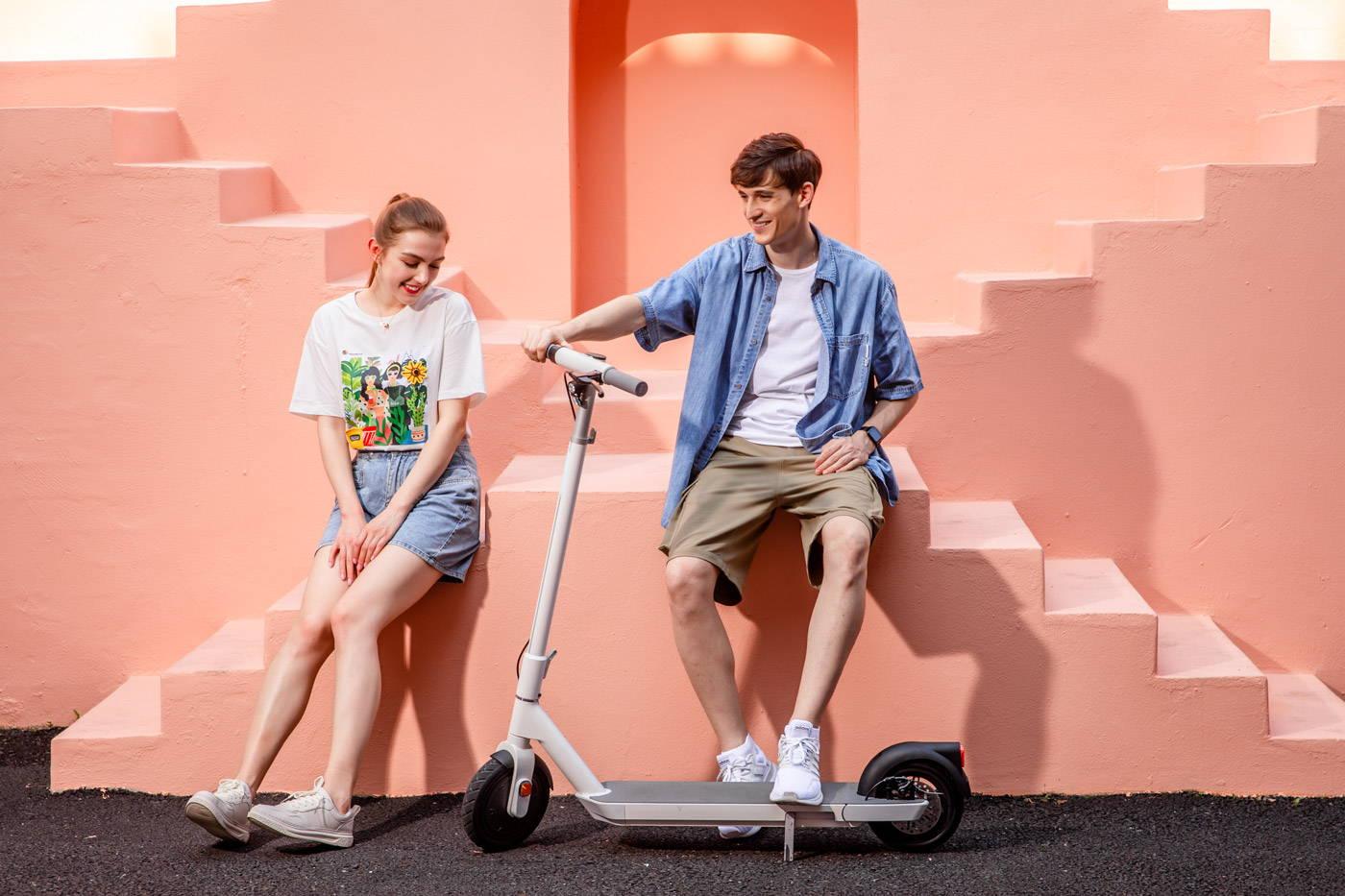 okai neon e-scooter couple smiling sitting