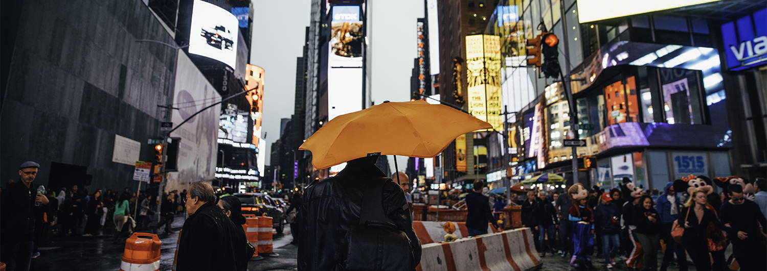 Man holding Blunt umbrella in Time Square