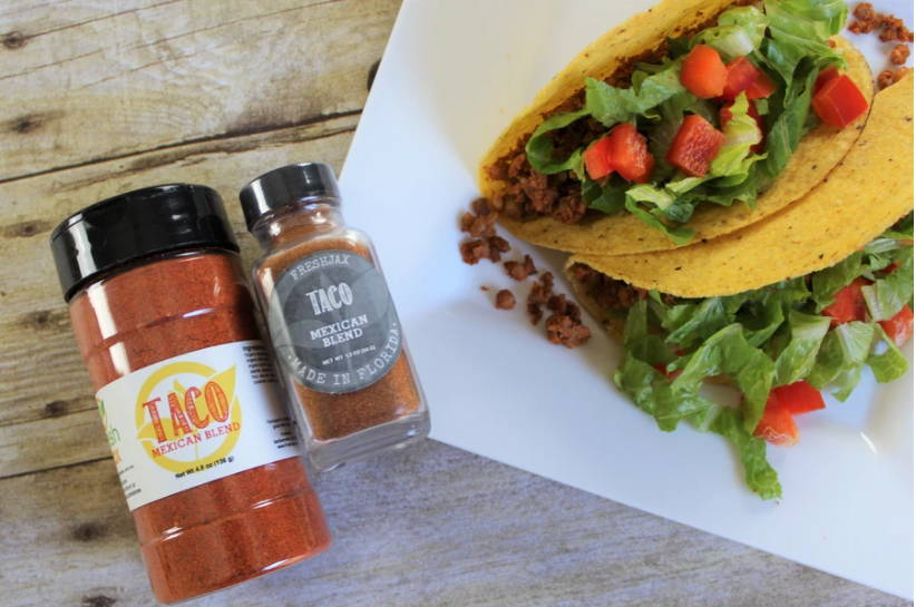 A large and sample size bottle of FreshJax Organic Taco Mexican Spice Blend next to a plate of two hard shell tacos filled with chickpeas, tomatoes, and lettuce.