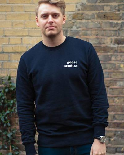 Man wearing navy blue organic cotton sweatshirt from sustainable brand Goose Studios