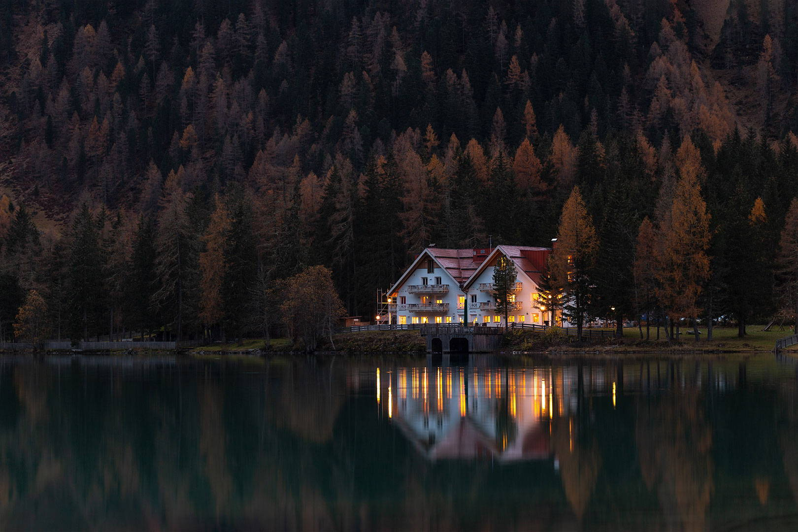 White and Red House  Surrounded by Trees and Lake at Twilight