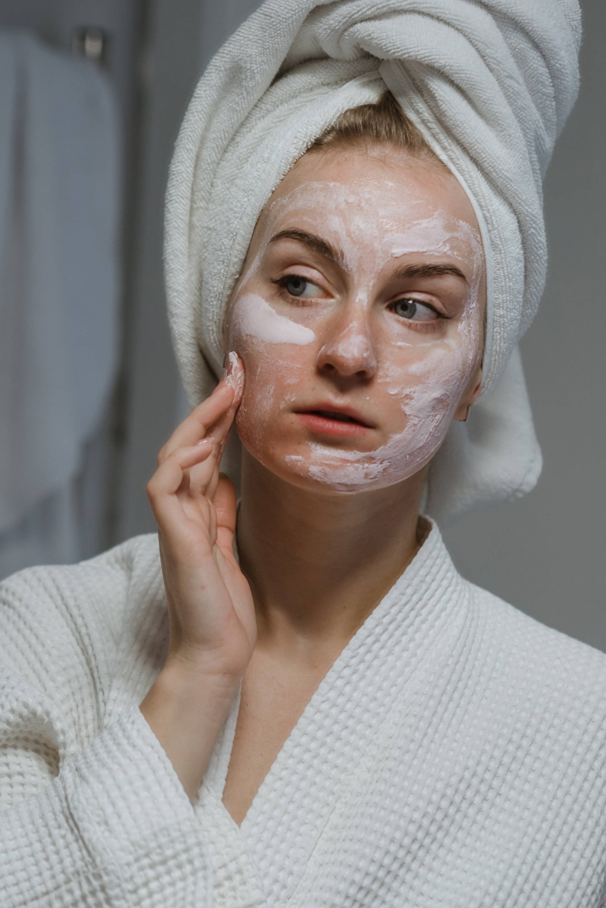 woman applying a face mask to her skin with her hair wrapped in a towel whilst looking in a mirror