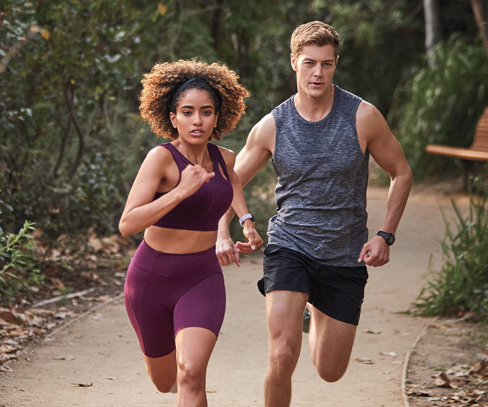 girl and boy in workout clothes running outside
