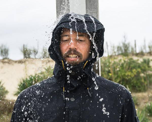 Man wearing Jeckbeng waterproof jacket made in black with water pouring on his head