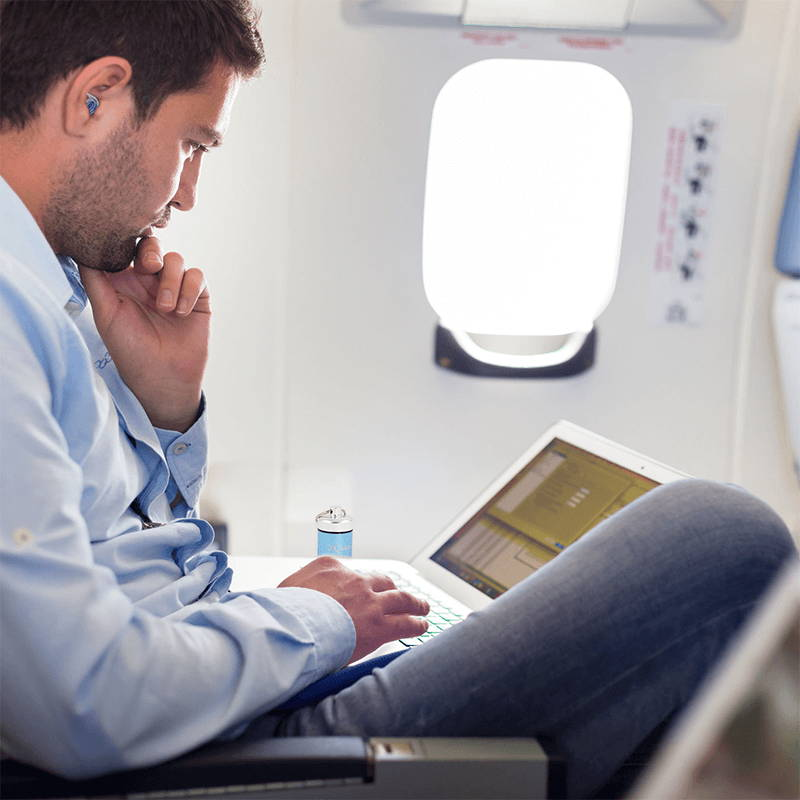 person working on their laptop on a plane while wearing ZQuiet Advanced Earplugs