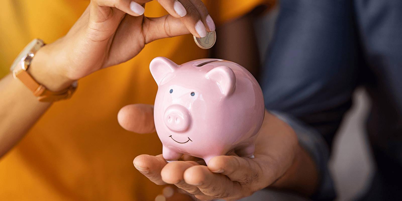 Close up of a couple putting a quarter in a piggy bank.