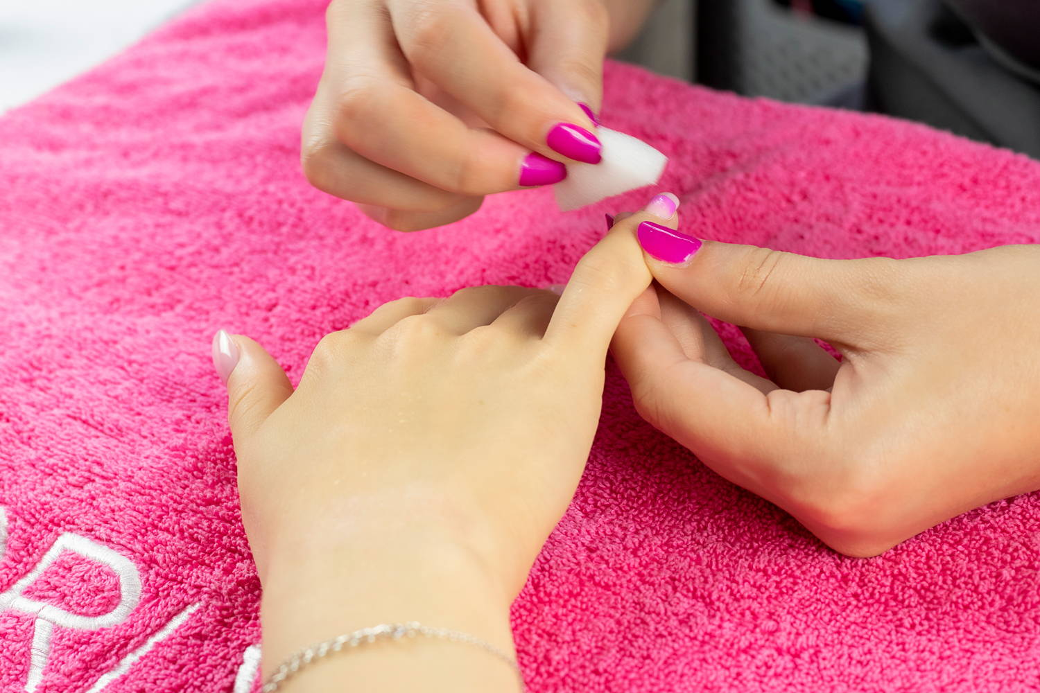 Nail technician using a sponge to create a nail fade design