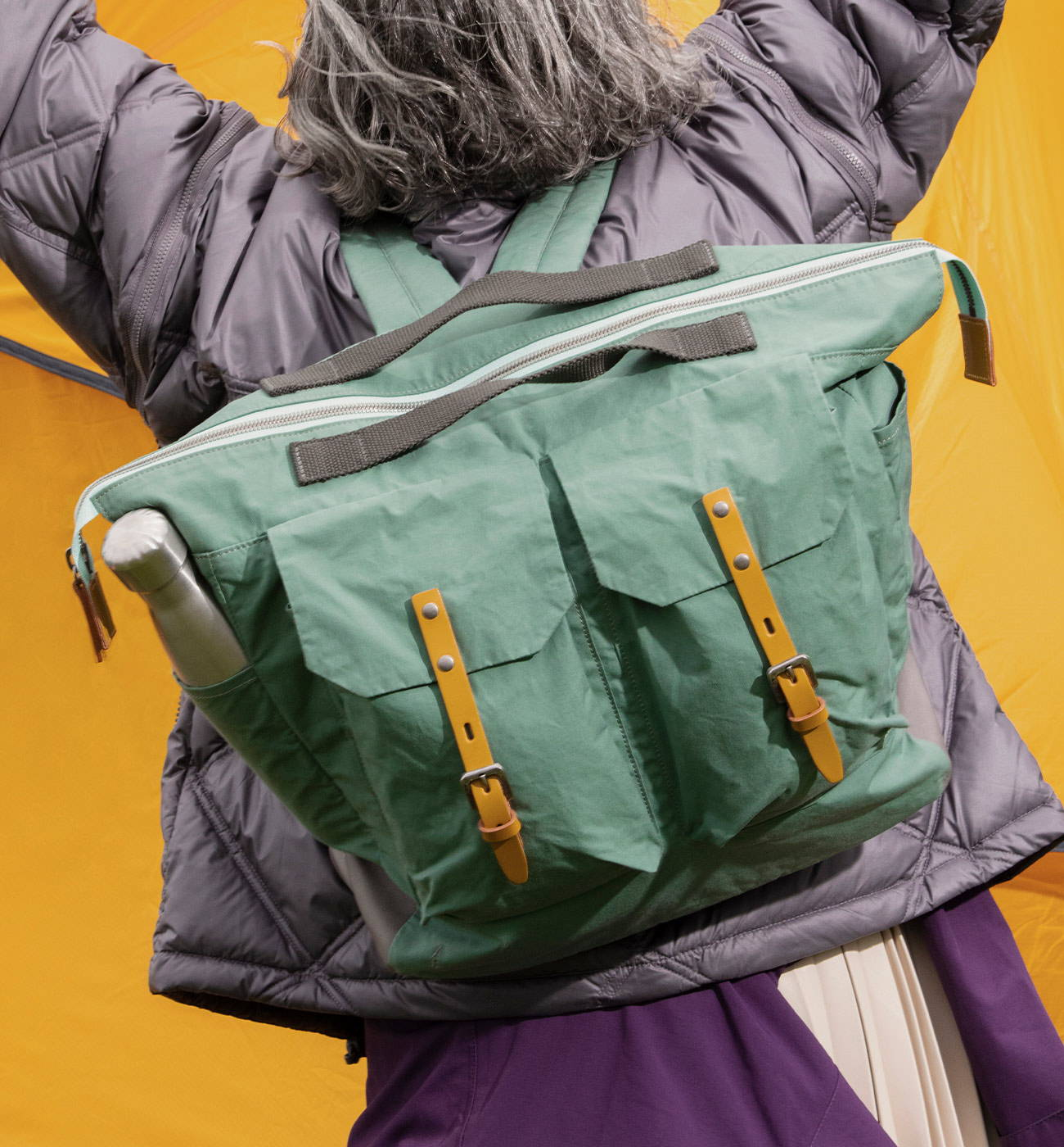 Model wearing Frank Large Waxed Cotton Backpack in Green