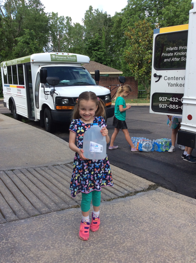 Kids carrying water bottles to the bus
