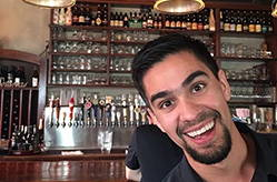 Eddie seems to be photobombing his own photo. He is enthusiastically smiling infront of a wall of taps and spirits.
