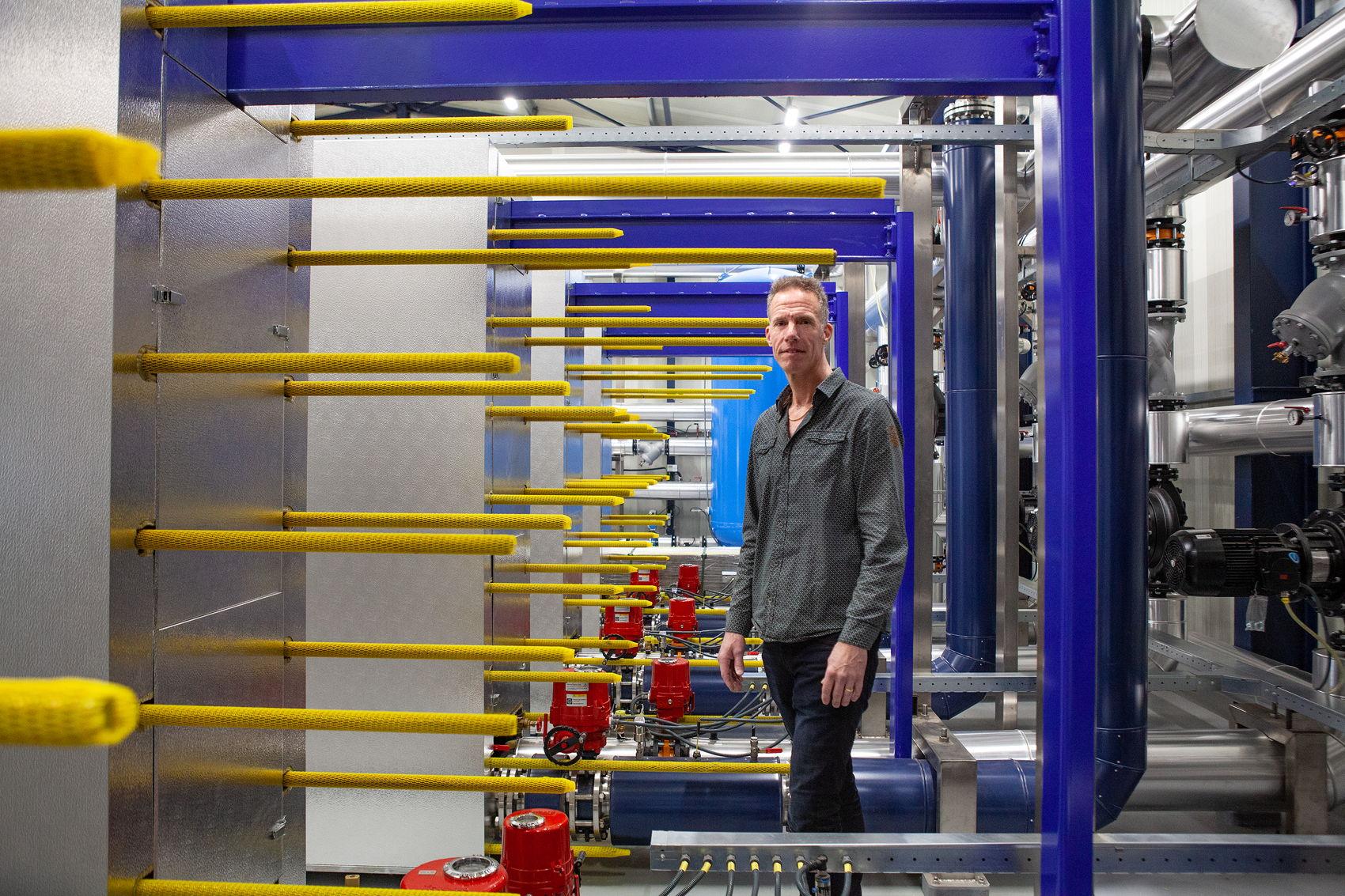 Foto van Paul tussen de warmtewisselaars van de geothermiecentrale