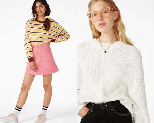 Woman wearing organic cotton t-shirt in burgundy, yellow and white with pink high waist zip up mini skirt and white tubular socks and light pink vans and woman wearing black jeans with a BCI cotton knitted oversized cream jumper, all from sustainable women's fashion brand Monki
