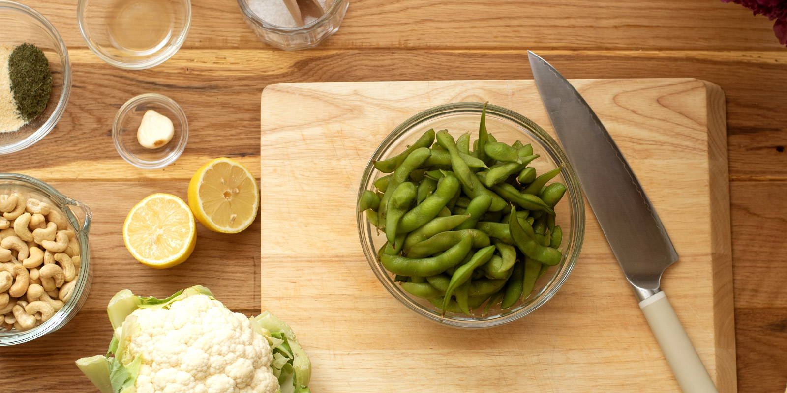 Bowl of edamame on cutting board surrounded by ingredients and a cutting knife.