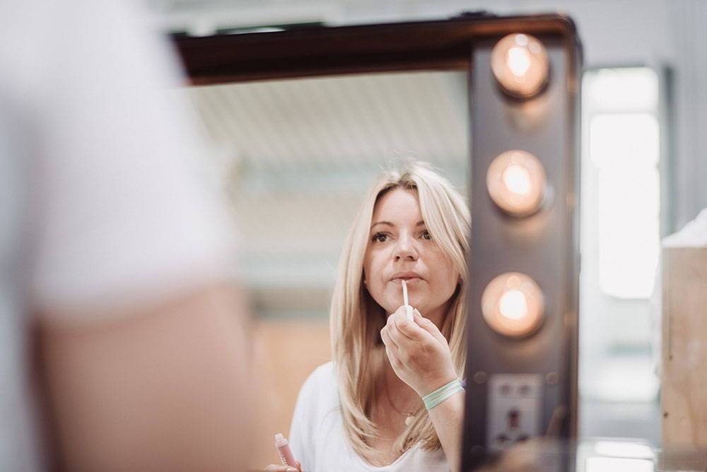 Frau schminkt ihre Lippen vor einem Spiegel