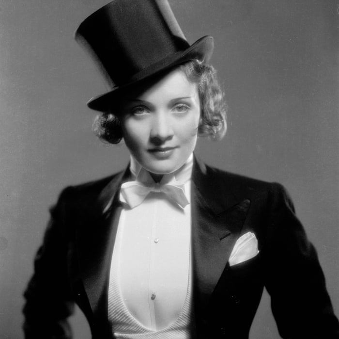 Black and white photograph of Marlene Dietrich wearing gazing into the camera wearing a tuxedo and top hat.
