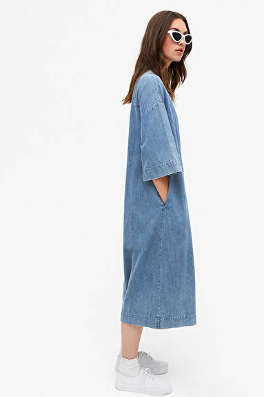 Side shot of woman wearing blue indigo organic cotton denim dress