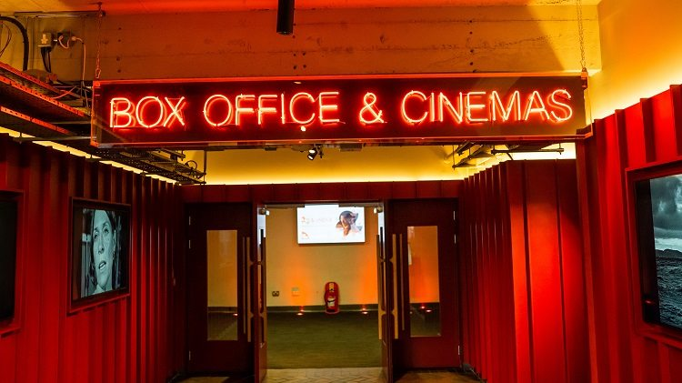 A neon sign reading 'box office and cinemas' above an open door.