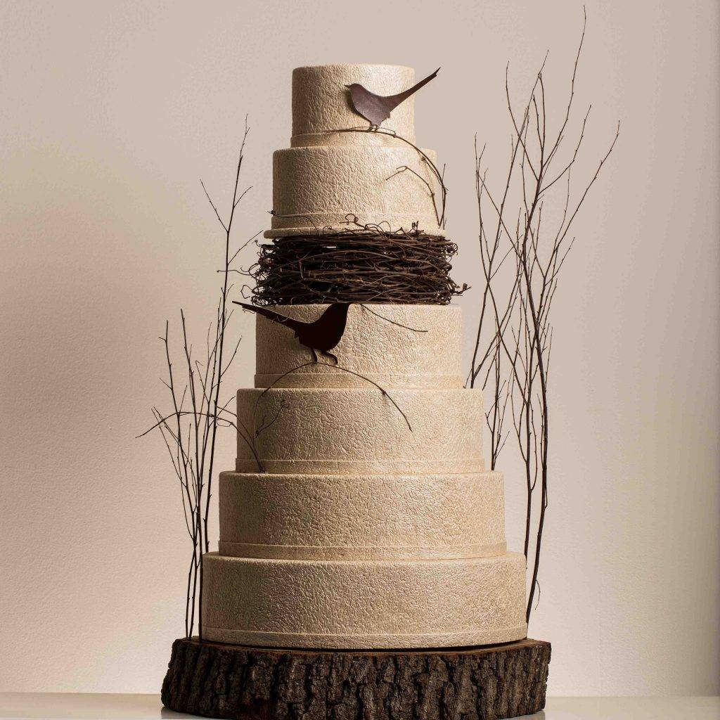 Multi-tiered wedding cake with a bird's nest theme.