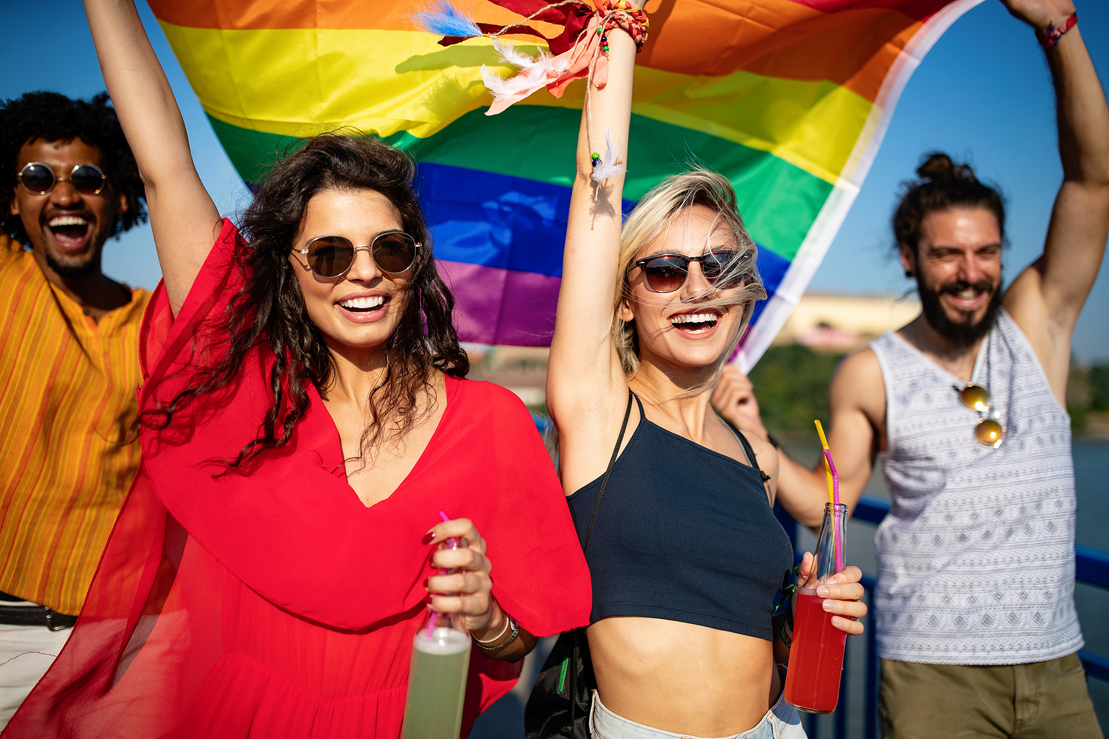 Image of an ethnically diverse group smiling walking together and holding a rainbow flag.