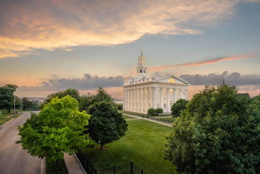 Angled photo fo the Nauvoo Temple facing West. Green trees fill the foreground.
