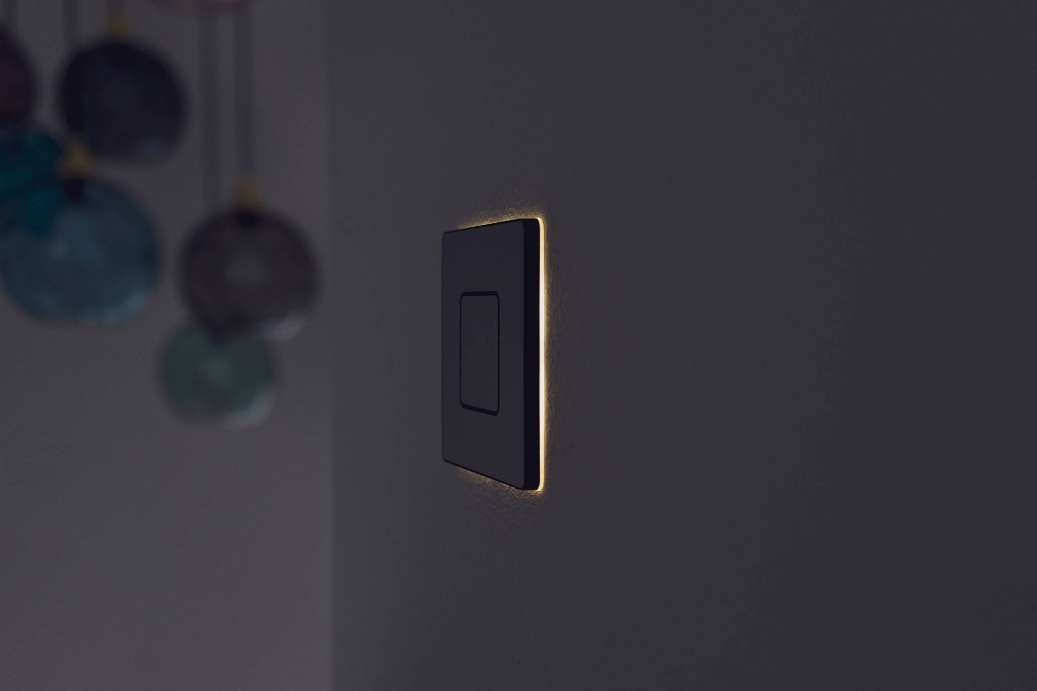 Faradite TAP 1 switch on wall with lights off on a Loxone smart home.