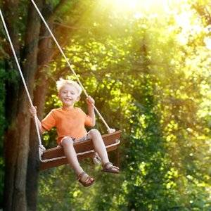 child swinging on tree swing offer to babysit as a great way to help a NICU mother