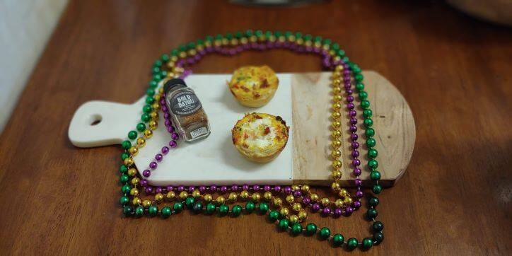 A cutting board with FreshJax Organic Bold Bayou Cajun Spice next to cajun mini quiches. Mardi Gras beads on table.