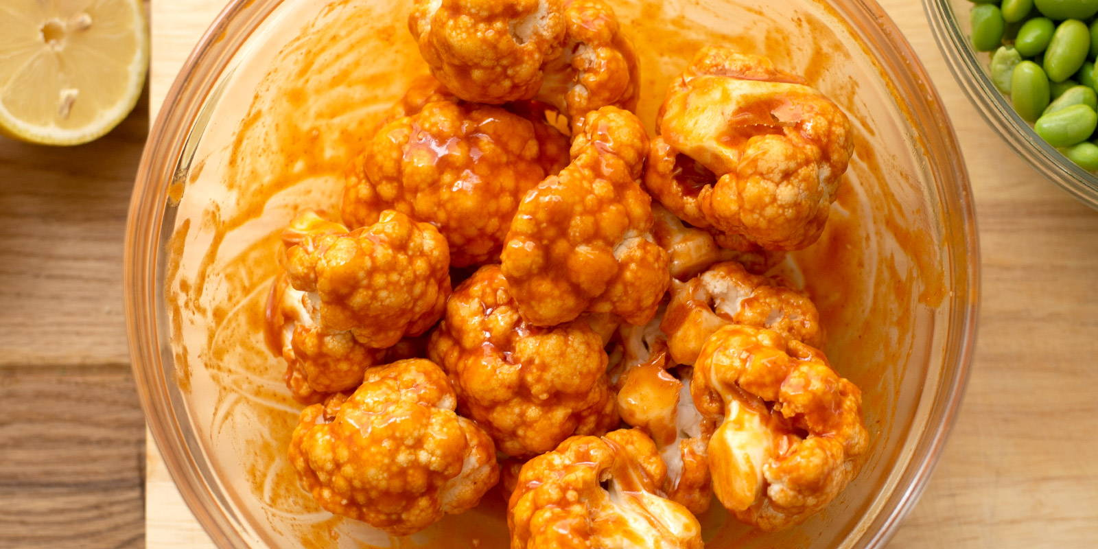 Bowl of cauliflower florets coated in buffalo sauce.