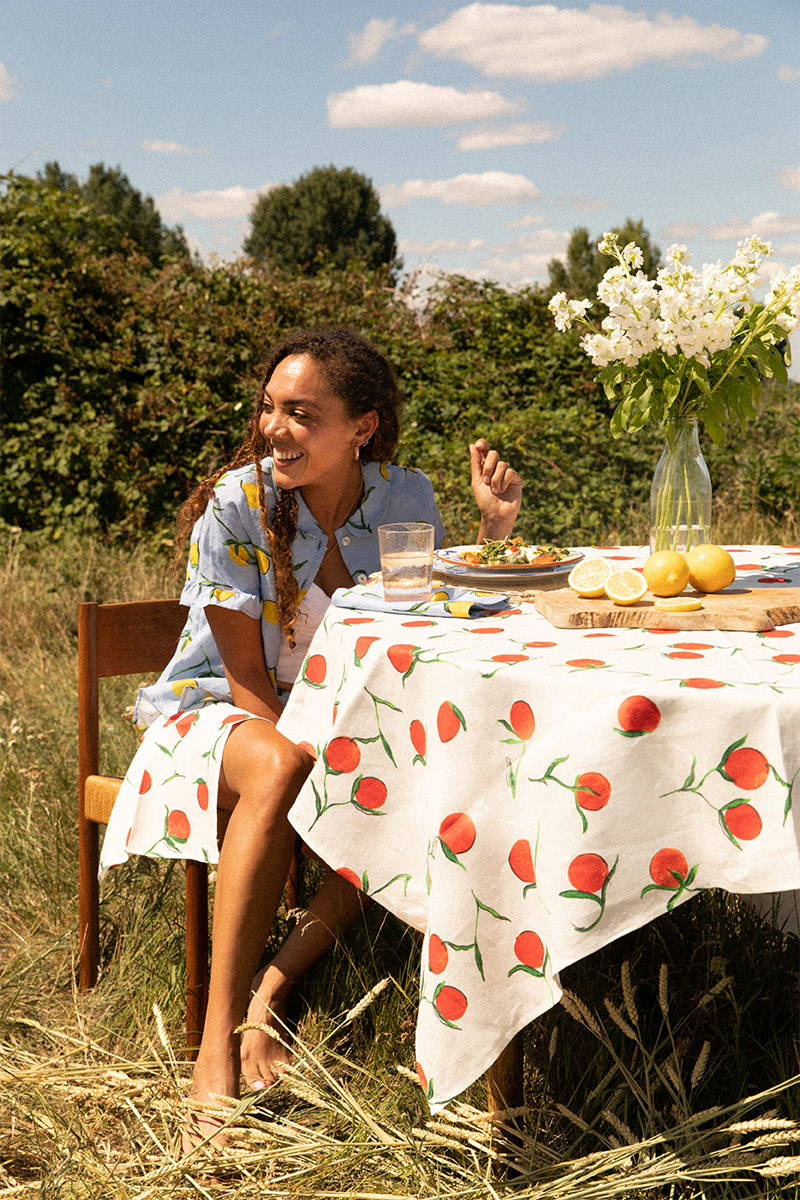 Miquita Oliver Sitting at a table dressed in YOLKE home and wearing matching daywear