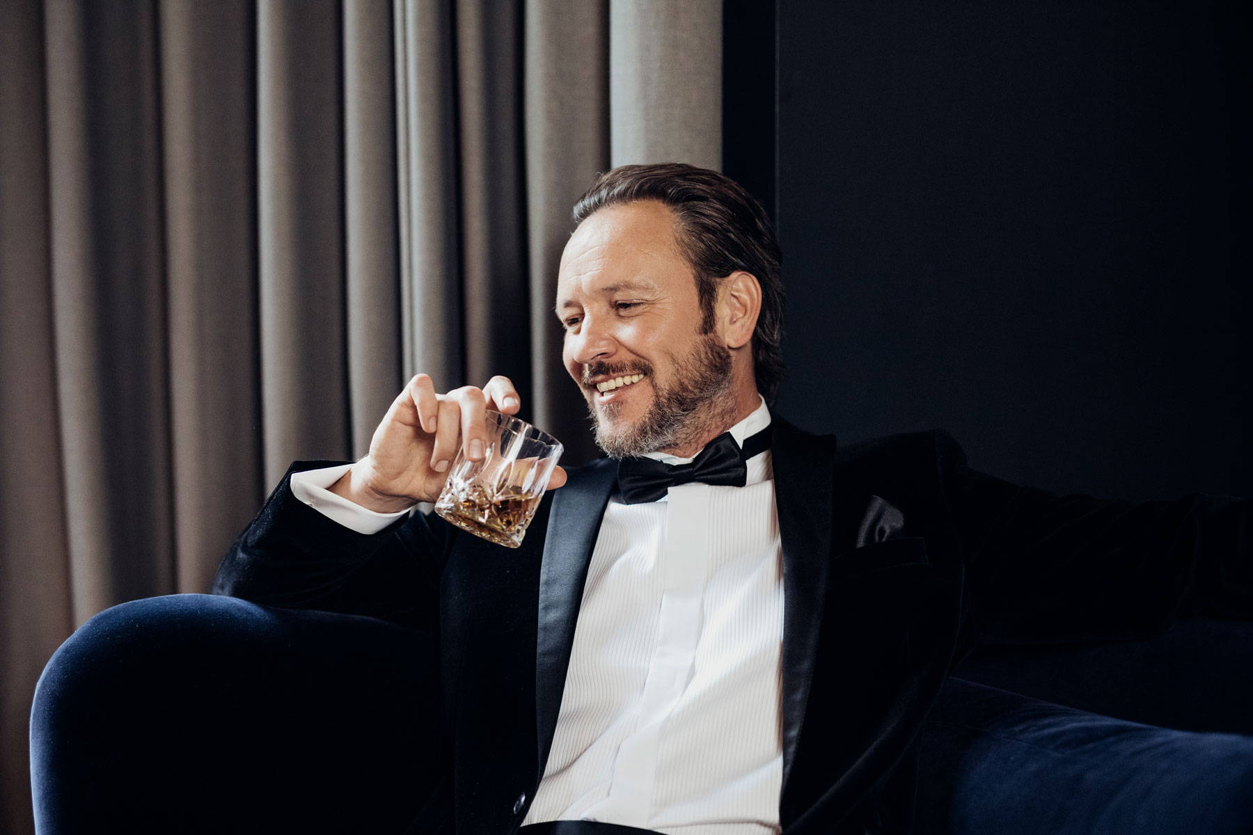 Gentleman drinking whiskey in suit