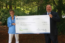 Mark Casady presents a $50,000 to Anne Springs Close, chairwoman of the nature preserve that will be adjacent to LPL's new home.