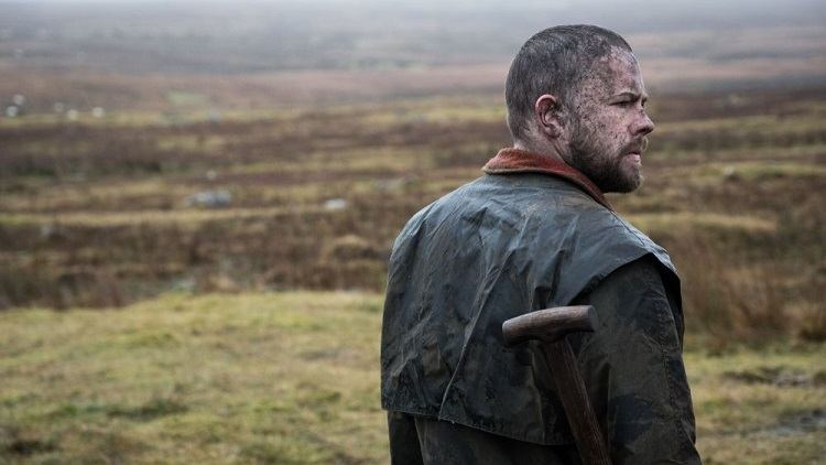 A man covered in mud stands on moorland holding a shovel.