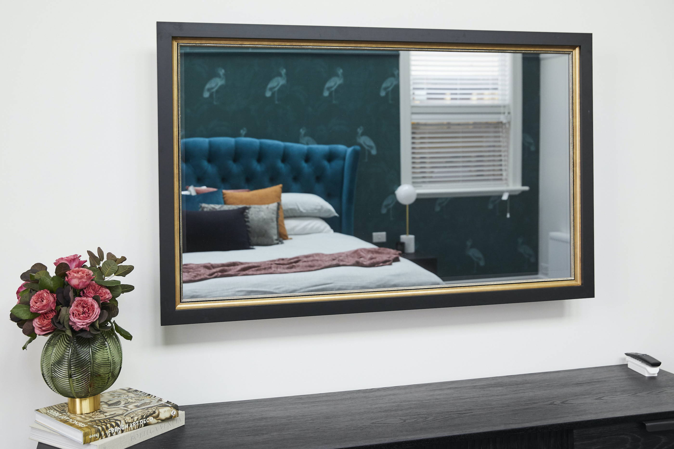 A close up TV-Mirror in a bedroom, reflecting a patterned wallpaper and velvet bedhead