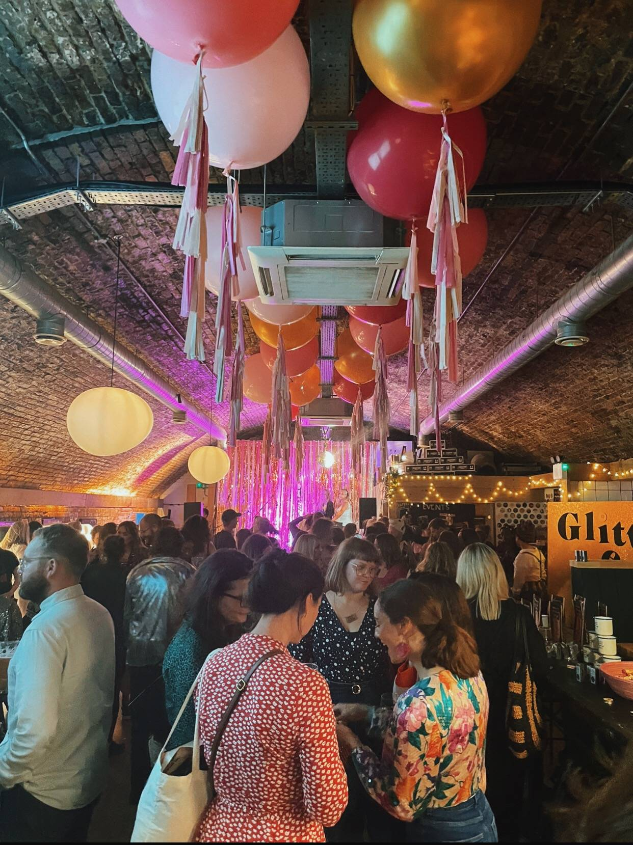 Image shows beautifully decorated venue with balloons, streamers, pink hues, and our biodegradable glitter bar.