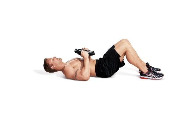 Lie on the floor holding a weight plate