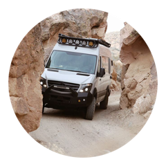 A Mercedes 144 Sprinter van with Flarespace flares installed drives through a rocky canyon